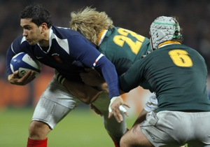 France's Maxime Mermoz, left, is tackled by Wynand Olivier, center, and Heinrich Brussow of South Africa during their international rugby union match in Toulouse, southwestern France, Friday, Nov. 13, 2009. (AP Photo/Christophe Ena)